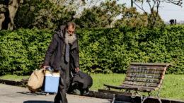 A homeless man walks in a park.