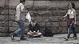 A homeless panhandler sitting down.
