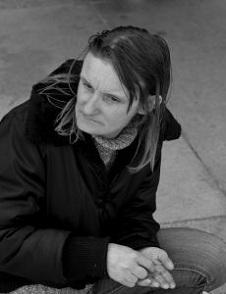 A homeless woman sits outside.