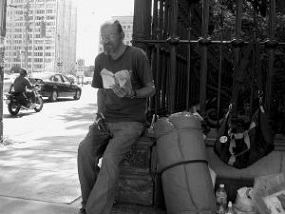 A homeless man sits on his luggage outside.