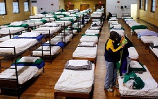A homeless shelter with rows of beds.