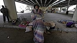 A cold man sits with a blanket wrapped around his body.