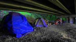 A row of tents are set up beneath a bridge.