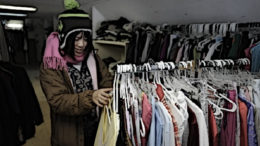 A woman searches a clothing rack at a homeless shelter.