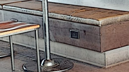 An electrical outlet is displayed on a bench.