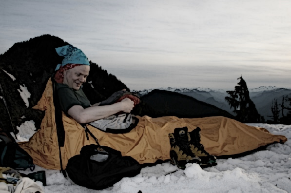 A man is sitting in a small tent on a mountain in snow.