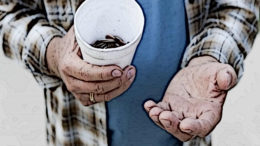 A man holds his change cup out to ask for money.