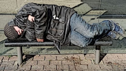 A homeless man sleeps on a bench.